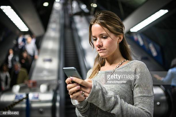 woman using a smartphone on the metro subway station