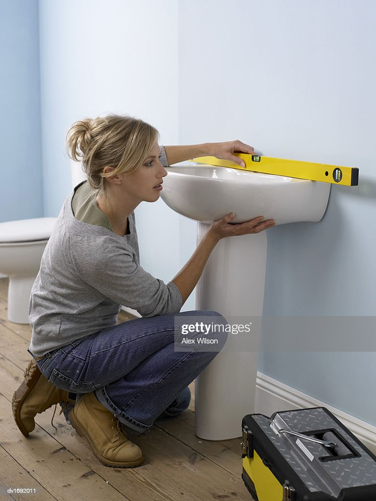 Woman Using a Spirit Level on a Sink in a Domestic Bathroom : Stock Photo