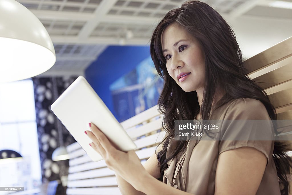 Woman using a tablet computer in a cafe : Stock Photo