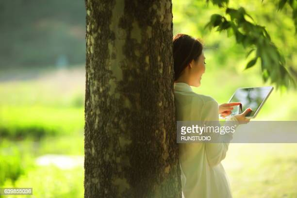 woman using a tablet in the park