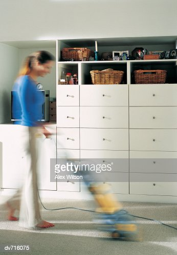 Woman Using a Vacuum Cleaner : Bildbanksbilder
