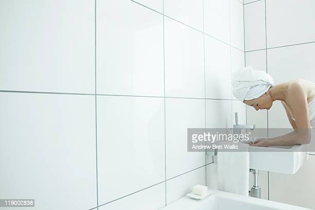 woman using a wash basin in a modern bathroom