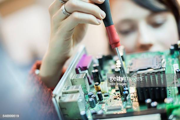 A woman using an electronic screwdriver on a computer circuit board.