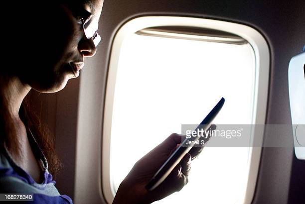 A woman using an ereader on a plane
