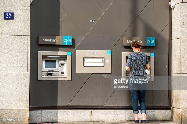 Woman using ATM on Oslo street, Norway