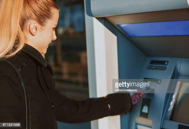 Femme utilisant un distributeur automatique de billets