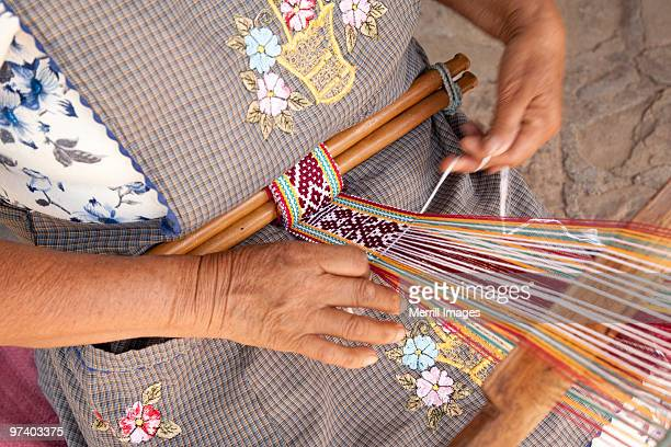 woman using backstrap loop to weave belt