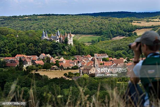 Woman using binoculars, focus on village and Castle of La Rochepot in background
