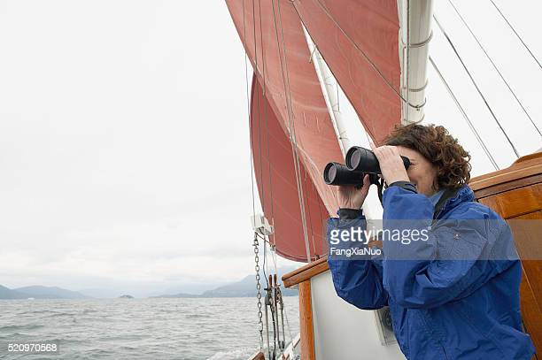 Woman using binoculars on a sailboat