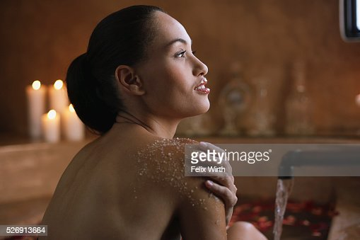 Woman using body scrub in bath : Stock Photo