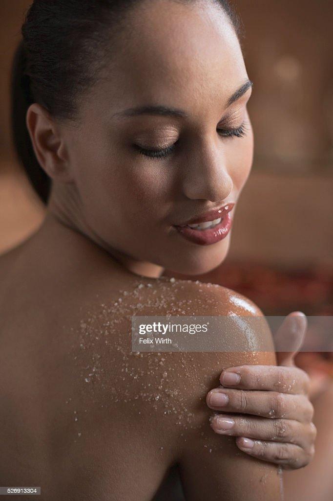 Woman using body scrub : Stock Photo