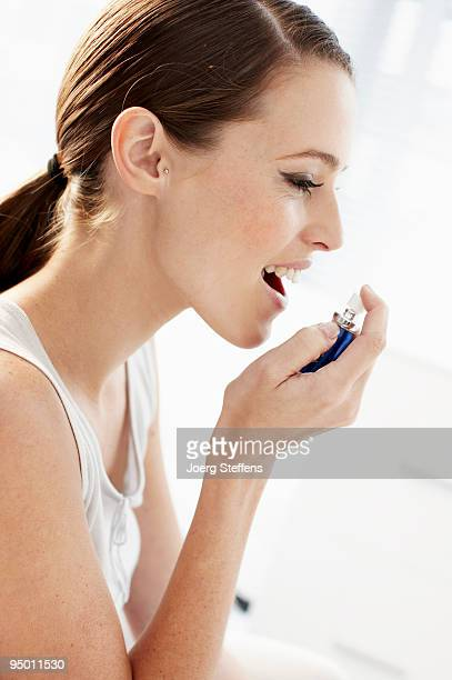 Woman using breath spray