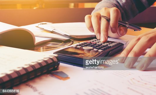 Woman using calculator with doing finance at home office. : Stock Photo
