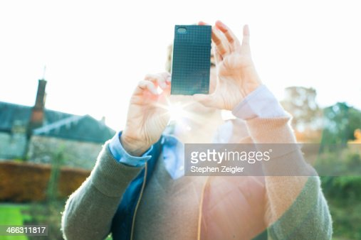 Woman using camera on mobile phone