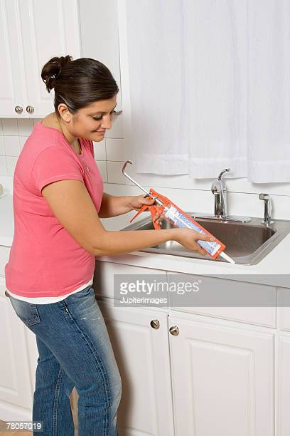 Woman using caulking gun around sink