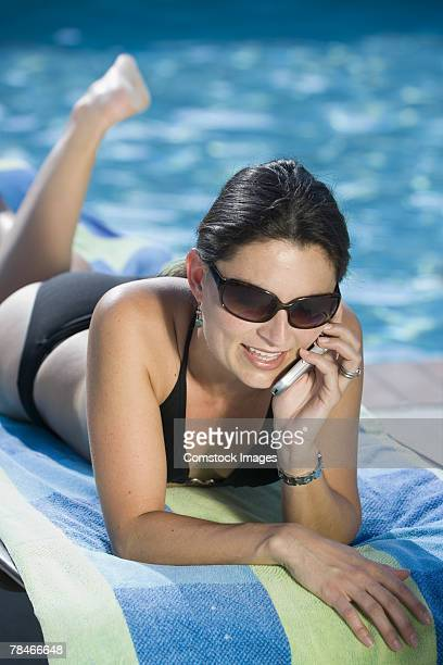 Woman using cell phone at poolside