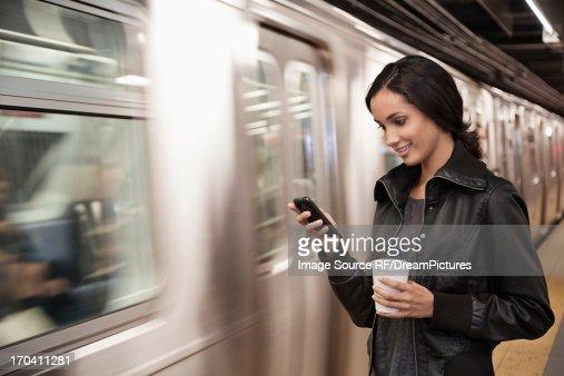 Woman using cell phone at subway station