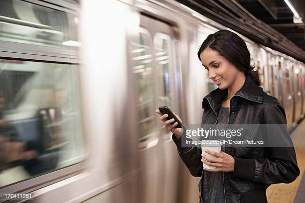 Woman using cell phone at subway station