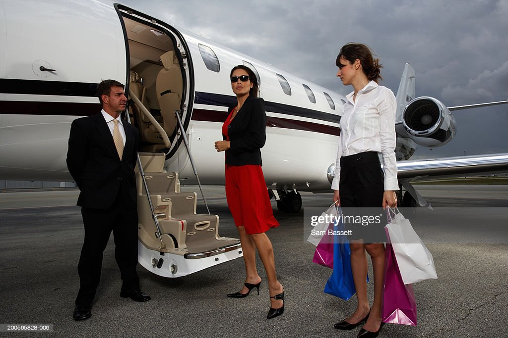 Woman using cell phone by plane, attendant holding shopping bags : Stock Photo