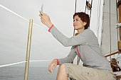 Woman using cell phone in sail boat