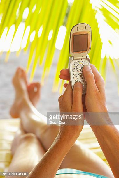 Woman using cell phone on beach, low section
