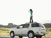 Woman using cell phone on roof of car, low angle view, Moab, Utah, USA