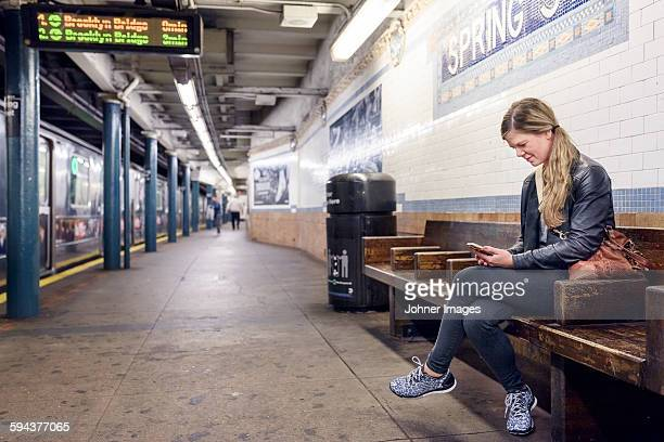 Woman using cell phone on train station. New York City, USA