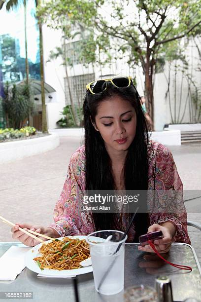 Woman using cellphone and eating