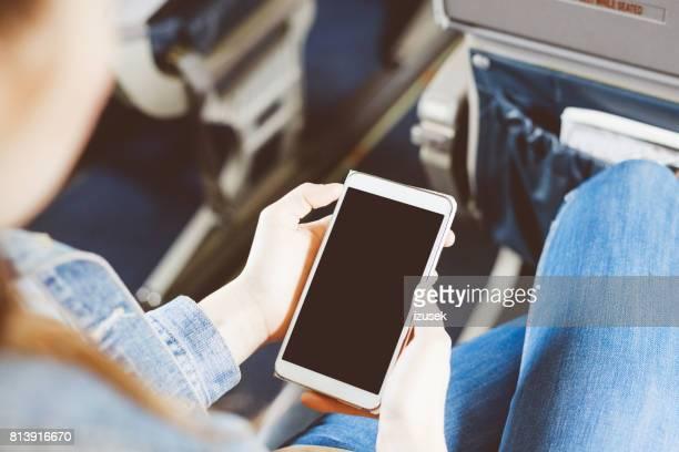 Vrouw met behulp van mobiele telefoon in vliegtuig