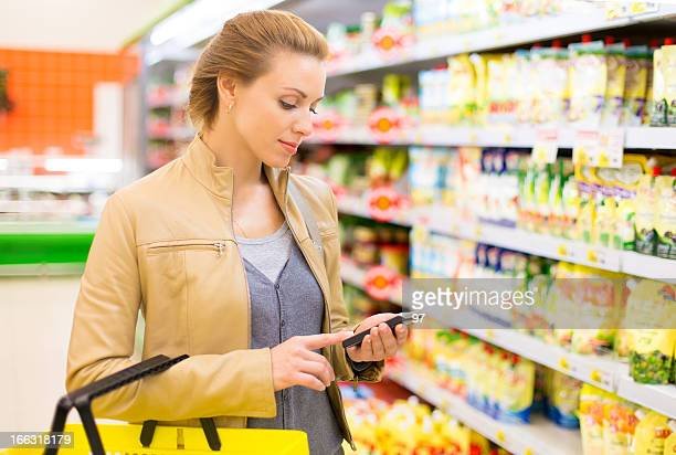 Woman using cellphone in supermarket.