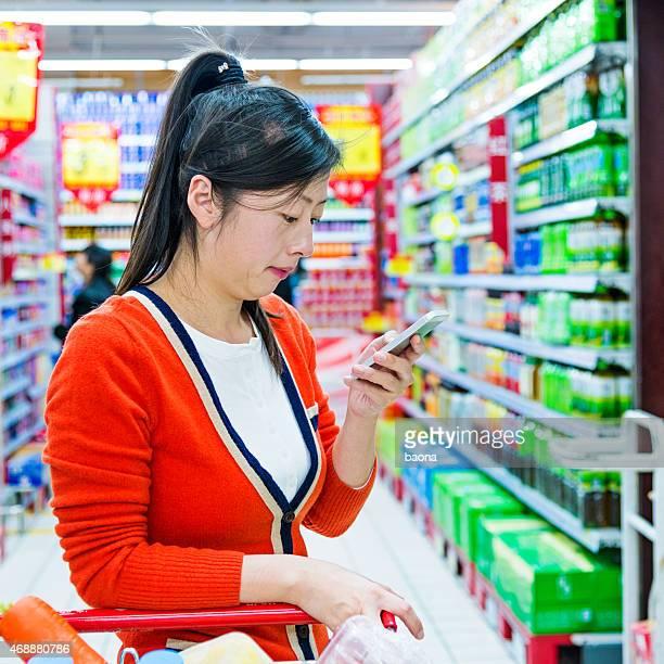 Frau im Supermarkt mit cellphone