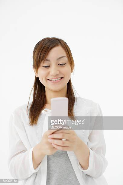 Woman using cellular phone, studio shot