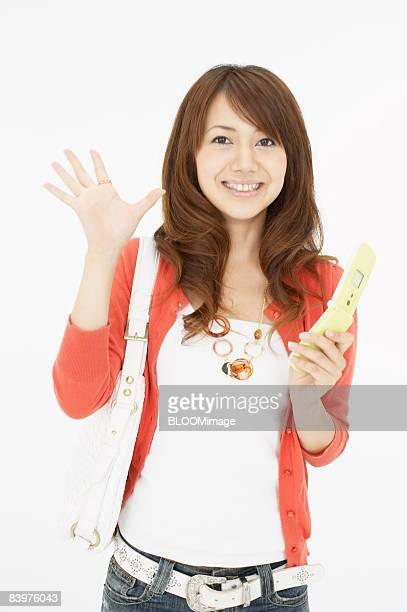 Woman using cellular phone, waving, studio shot