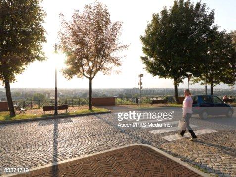 Woman using cobblestone pedestrian crossing : Stock Photo