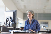 Woman using computer at desk in office, smiling