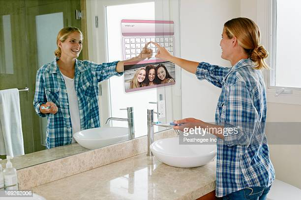 Woman using computer in mirror