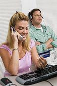Woman Using Computer While Husband Uses mp3 player