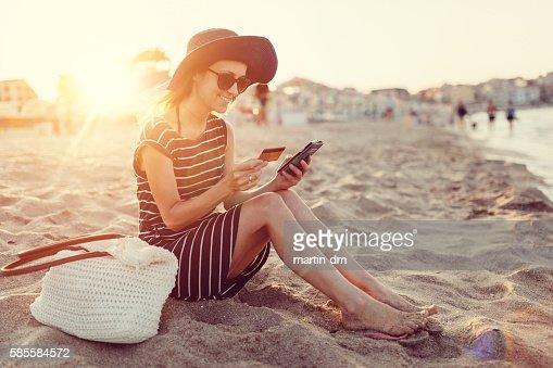Woman using credit card at the beach