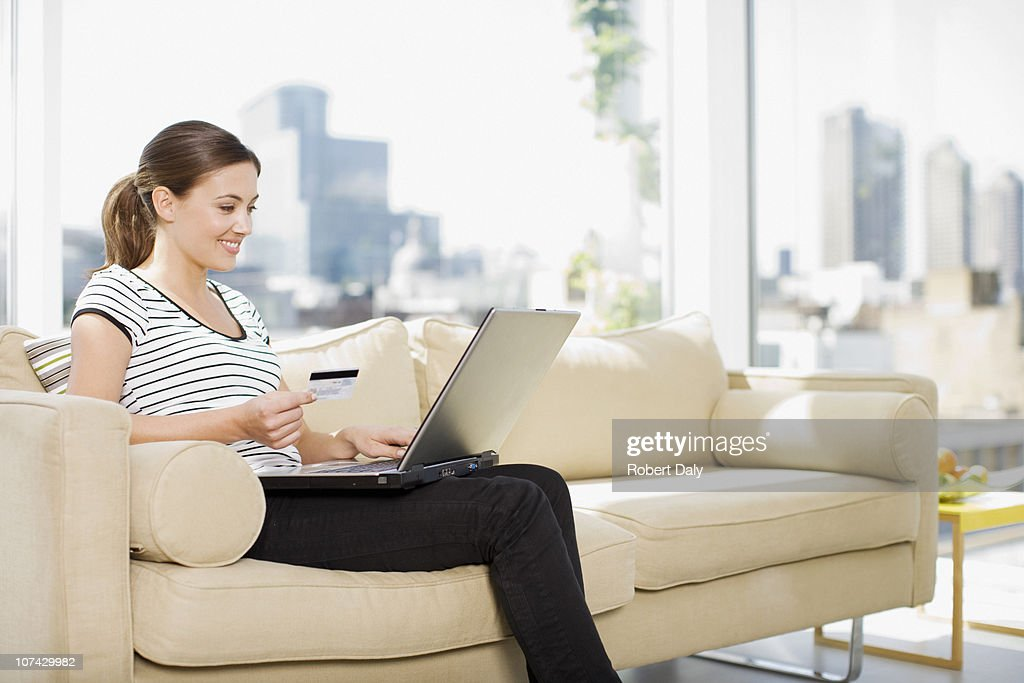Woman using credit card to purchase merchandise on internet : Stock Photo