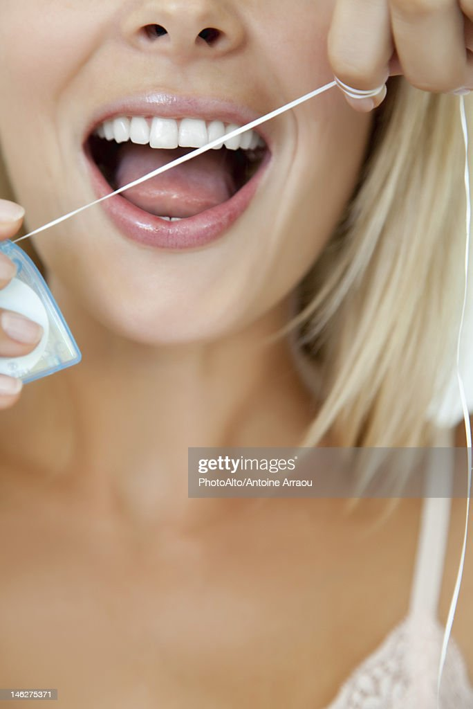 Woman using dental floss, cropped