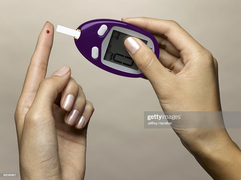 Woman using diabetes test kit : Stock Photo