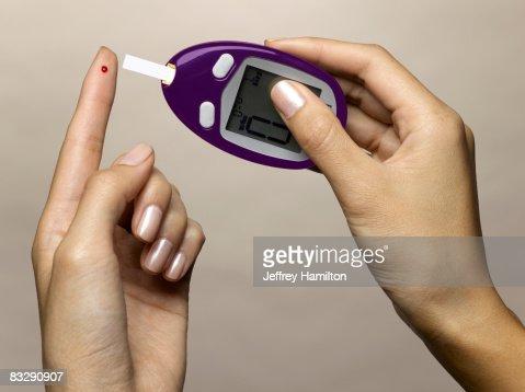 Woman using diabetes test kit : Stock Photo