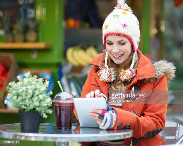 Woman using digital tablet at juice bar.