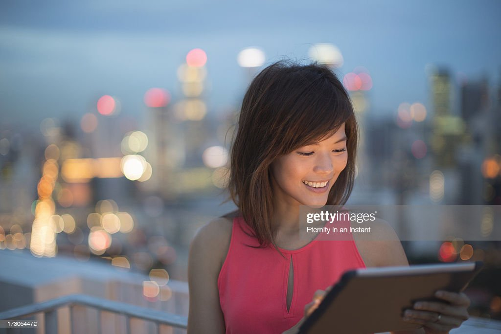 Woman using digital tablet at night in city : Stock Photo