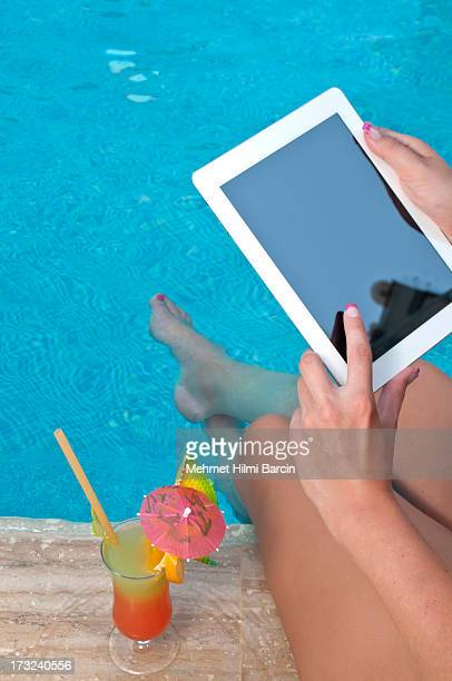 Woman using digital tablet by the pool