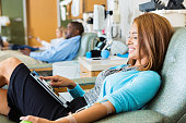 Woman using digital tablet in busy hospital blood donation bank