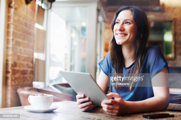 Woman using digital tablet in cafe.