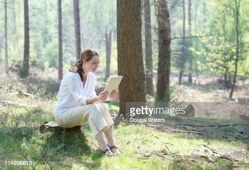 Woman using digital tablet in forest. : Stock Photo