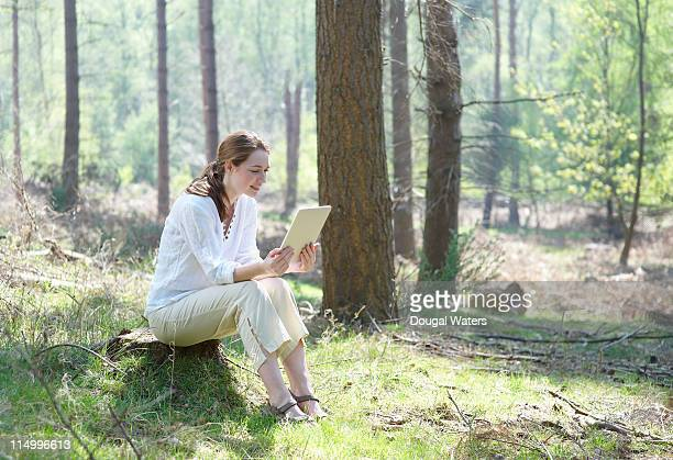 Woman using digital tablet in forest.