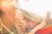Woman using digital tablet in hammock